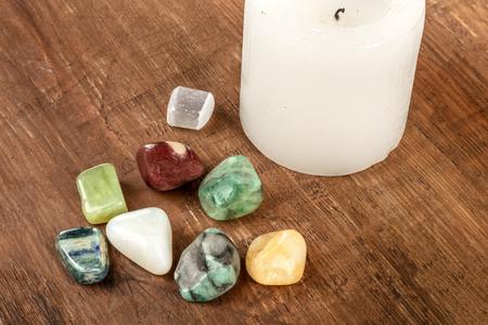 Semiprecious gemstones on a dark wooden background with candle and copy space Zdjęcie Seryjne