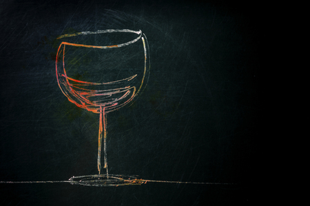 A photo of a simple drawing of a glass of wine, made with chalk on a blackboard, with copy space