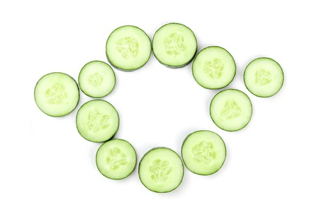 Cucumber slices in circle on white background with copy space
