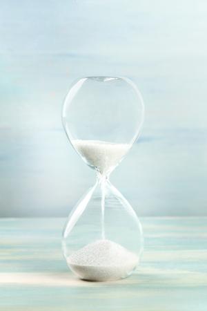 Una vista lateral de un reloj de arena con arena que cae, sobre un fondo verde azulado con espacio de copia Foto de archivo