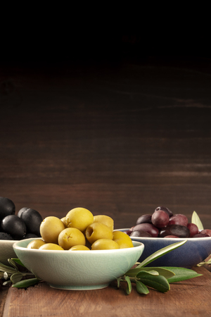 Photo of various olives in bowls with copy space