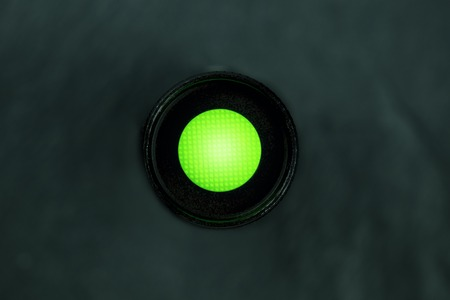 An overhead photo of a vibrant green button on a dark panel with copy space Foto de archivo