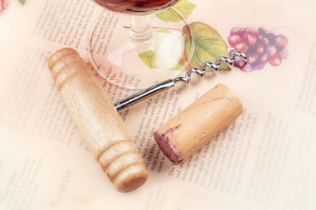 A photo of a vintage corkscrew, a cork, and a glass of wine, shot on a blurred vintage newspaper with a drawing of a bunch of grapes on a vine