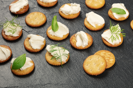 A photo of salt crackers with soft spreadable cream cheese and herbs on a black background with copy space Archivio Fotografico - 109236221