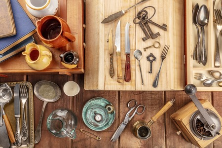 An overhead photo of many vintage objects, flea market stuff on a wooden background