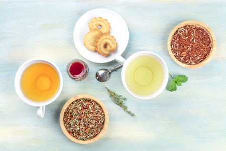Tea tasting. Various cups of tea and loose dry tea leaves with cookies, jam, and copy space Stock Photo