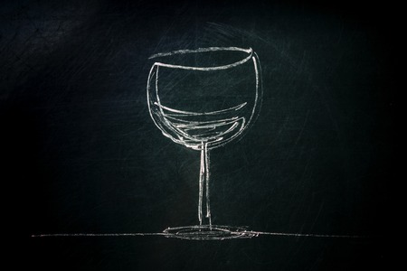 A photo of a simple drawing of a glass of wine, made with chalk on a blackboard, with copyspace