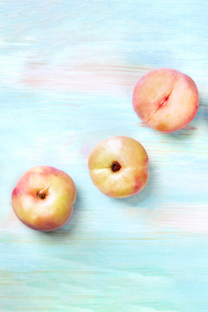 An overhead photo of vibrant organic flat saturn peaches, shot from above on a teal background with copyspace Stock Photo