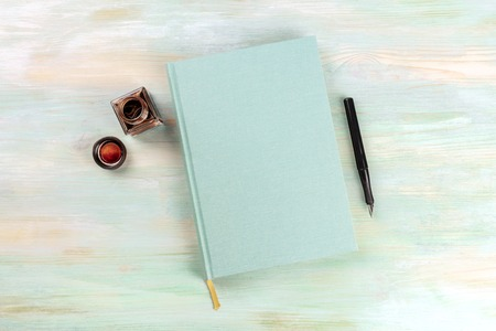 An overhead photo of an ink well with a teal journal, with a nib pen and a place for text 版權商用圖片