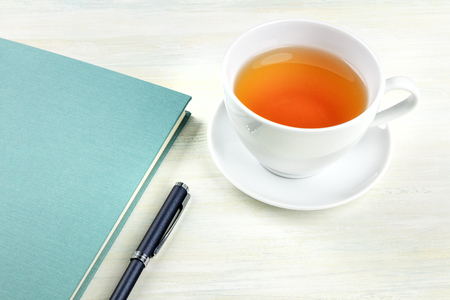 A photo of a journal with a pen and a cup of tea, with copy space