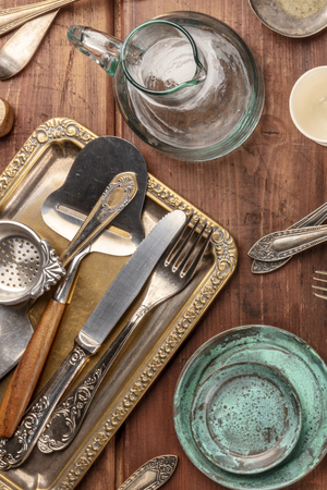 A top shot of many vintage kitchen objects and cutlery from an old restaurant, flea market stuff on a wooden table