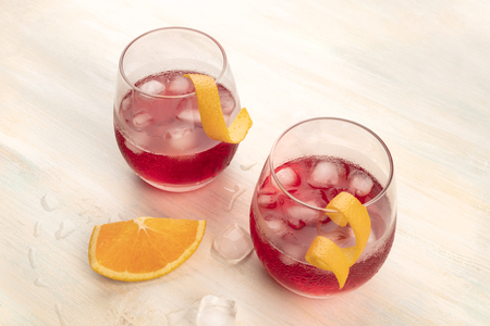 Two vibrant cocktails with  orange zest garnishes, with ice cubes on a light background, with copy space