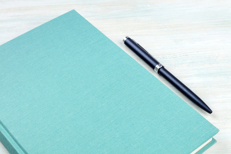 A photo of a teal blue journal with a pen, an elegant notebook or planner with copy space