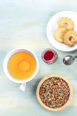A cup of tea and loose dry tea leaves with cookies, jam, and copy space