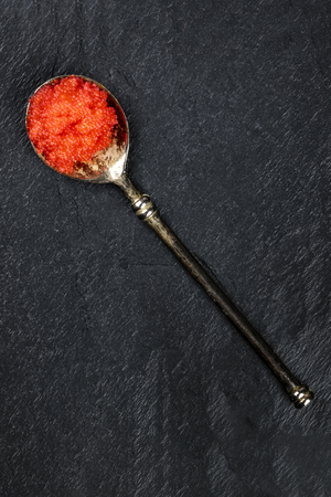 Red fish caviar in a vintage spoon, shot from the top on a black background with copyspace Zdjęcie Seryjne