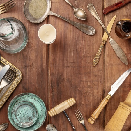 A photo of many vintage kitchen objects and cutlery from an old restaurant, flea market stuff, shot from the top on a wooden background with a place for text