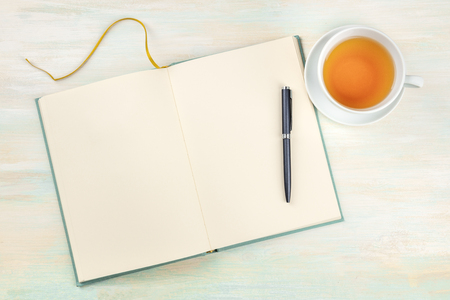 A photo of an open journal with a pen and a cup of tea, shot from above, on a light background with copy space