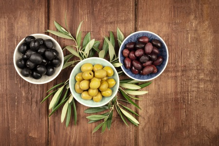 Various olives in bowls with leaves, shot from the top on a dark rustic wooden background with a place for text