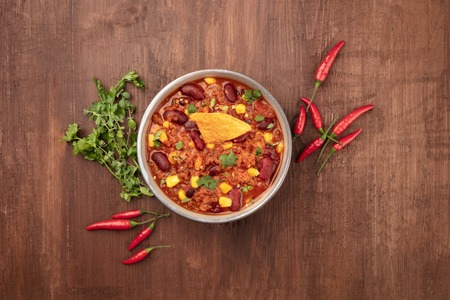 Chili con carne, traditional Mexican dish, shot from the top on a dark wooden background with ingredients and copy space