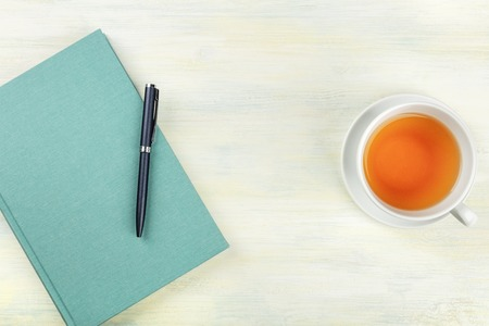 A photo of a teal blue journal with a pen and a cup of tea, shot from above, forming a frame on a light background with copyspace 스톡 콘텐츠