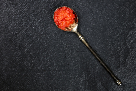 Red fish caviar in a vintage spoon, shot from above on a black background with a place for text