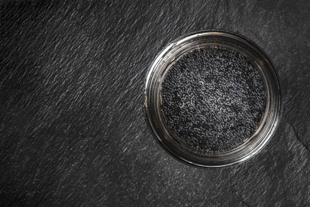 Black fish caviar in a jar, shot from above on a black background with a place for text