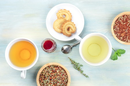 Tea tasting. Various cups of tea and loose dry tea leaves with cookies, jam, and a place for text Stock Photo
