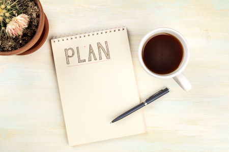 An overhead photo of a spiral notebook with the word Plan, with a cup of coffee and a blooming cactus plant, shot from above on a desk with copy space, a planning mockup