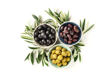 Overhead photo of various olives in bowls on a white background with a place for text