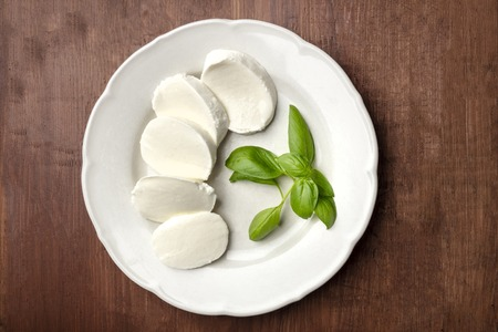 A photo of a white plate with fresh basil leaves and Mozzarella cheese, shot from the top on a dark rustic wooden background with copy space