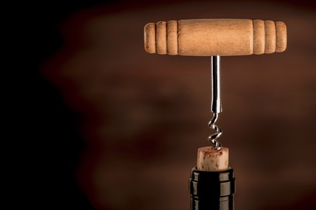 A closeup photo of a vintage corkscrew in a bottle of wine, on a dark background with copy space. Toned image