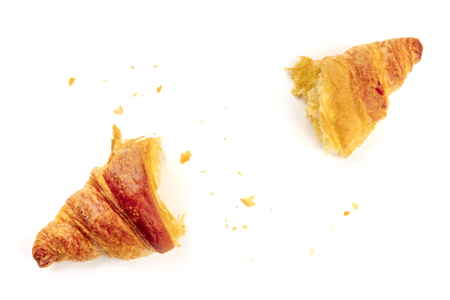 A photo of a croissant torn in two halves to see the texture, shot from the top on a white background with a place for text