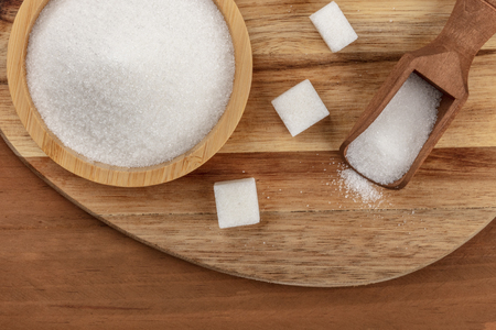 An overhead closeup photo of a bowl and a scoop of white sugar, with sugar cubes, shot from above on a dark rustic wooden background with a place for text