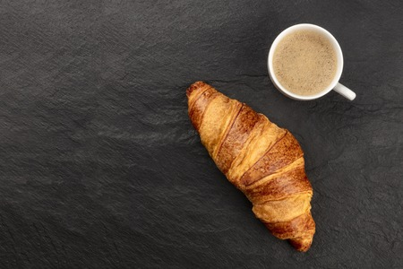 Good Morning. A photo of a croissant with a cup of coffee, shot from above on a black background with copy space 免版税图像