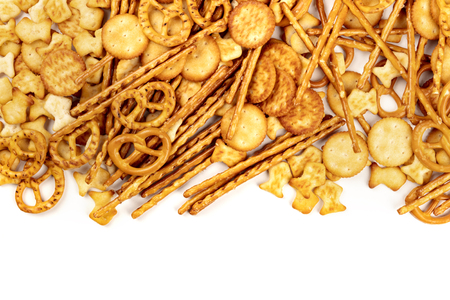 An assortment of salt crackers, sticks, pretzels, and goldfishes, shot from above on a white background with copy space. Salty party snacks mix with a place for text Stock Photo