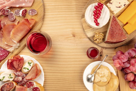 Charcuterie Tasting. A photo of many different sausages and hams, lunch meats, and a cheese platter, shot from above on a rustic background with a glass of red wine and copy space Stock Photo