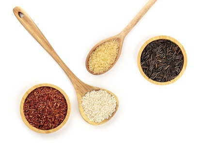 A photo of various types of rice, shot from the top on a white background with copy space