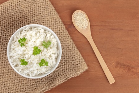 A photo of a bowl of cooked white long rice, shot from the top on rustic textures with a wooden spoon with dry rice and copy space