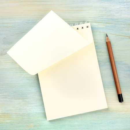 Turning a New Page. A photo of a spiral note pad with a blank sheet of paper, shot from above on a teal blue background with a lead pencil and copy space