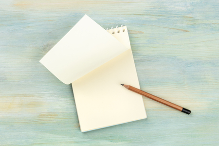 A New Page Turned. A photo of a spiral note pad with a blank sheet of paper, shot from the top on a teal blue background with a sharp pencil and a place for text