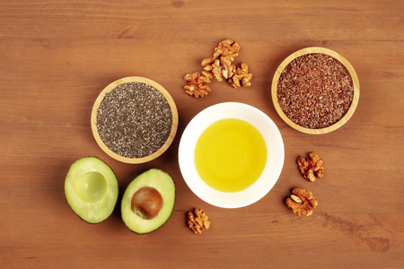 An overhead photo of healthy omega 3 vegan diet food. Avocado, walnuts, chia and flax seeds, shot from the top on a dark rustic background with a place for text