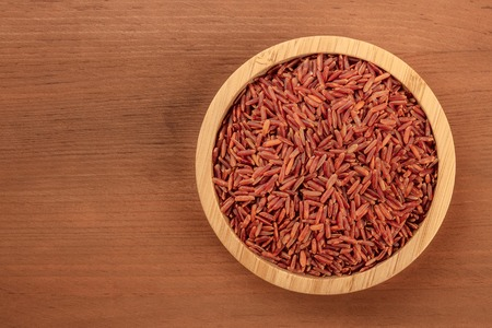 A photo of a long grain red rice, shot from above in a wooden bowl on a dark rustic background with copy space
