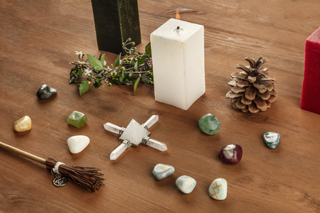 Witchcraft. A photo of a Wicca altar with candles, crystal stones, and Norse runes, with a little broom with a pentacle, on a dark rustic wooden background with a place for text