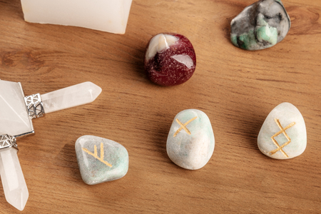 A closeup of ancient Norse runes, stones with symbols used in Wicca and other magic and for divination, with mysterious crystals Stock Photo