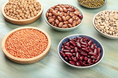 Various types of legumes on a teal background. Red kidney beans, lentil, chickpea, soybeans, black-eyed peas Stock Photo