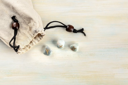 Norse runes, stones with symbols used in Wicca and other magic and for divination, tossed from a bag, shot from the top on a light background with a place for text
