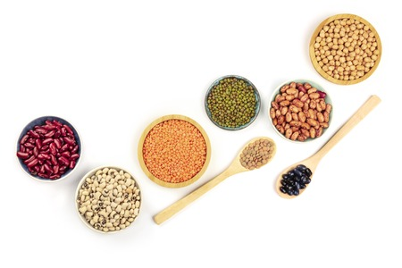 Various types of legumes, shot from above on a white background with copy space. Red kidney beans, lentils, chickpeas, soybeans, black eyed peas