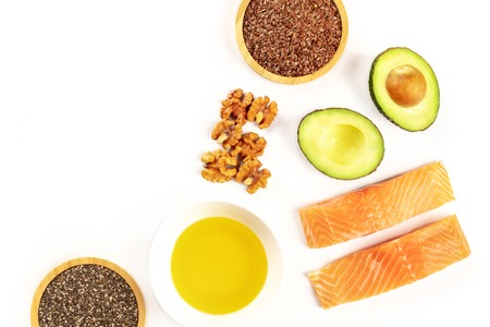 Food, rich in omega-3 fatty acids. Raw salmon, avocado, walnuts, chia and flax seeds, shot from the top on a white background with a place for text