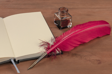 Writing Poetry. A photo of a quill with and ink well and an open book on a wooden table with a place for text 版權商用圖片