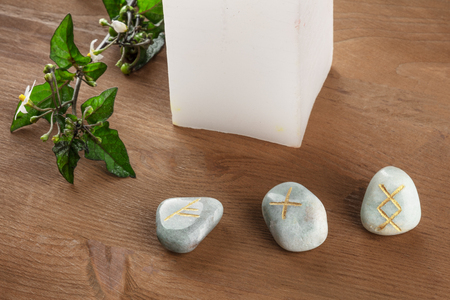 A closeup photo of Norse runes, stones with symbols used in Wicca and other magic and for divination, with a candle on a dark rustic background with a place for text Zdjęcie Seryjne
